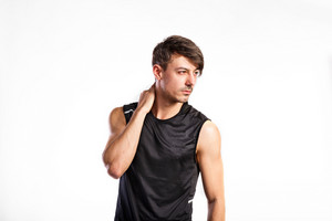 Handsome hipster fitness man in black tank top shirt, holding neck. Studio shot on gray background.