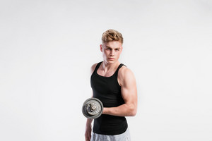 Handsome hipster fitness man in black tank top shirt working out with dumbbell. Studio shot on gray background.
