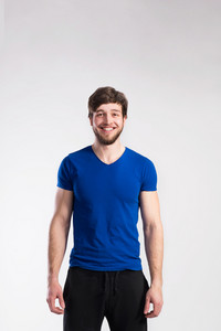 Handsome hipster fitness man in blue t-shirt. Studio shot on gray background.