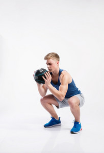 Handsome hipster fitness man in blue tank top shirt and gray shorts holding medicine ball, doing squat. Studio shot on gray background.