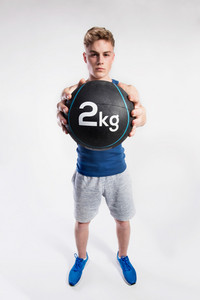 Handsome hipster fitness man in blue tank top shirt and gray shorts holding medicine ball. Studio shot on gray background.