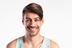 Handsome hipster fitness man in blue tank top shirt smiling. Studio shot on gray background.