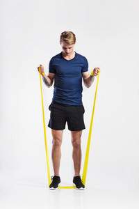 Handsome hipster fitness man in dark blue t-shirt and black shorts working out with resistance bands. Tattoo on his forearms. Studio shot on gray background.