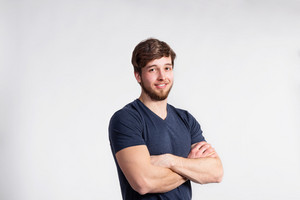 Handsome hipster fitness man in gray t-shirt, arms crossed. Studio shot on gray background.