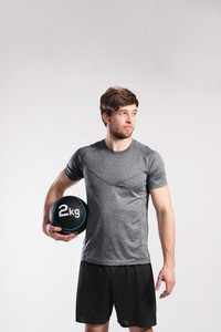 Handsome hipster fitness man in gray t-shirt holding medicene ball. Studio shot on gray background.