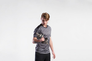 Handsome hipster fitness man in gray t-shirt working out with dumbbell. Studio shot on gray background.