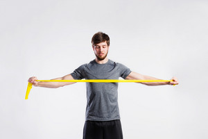 Handsome hipster fitness man in gray t-shirt working out with rubber band. Studio shot on gray background.