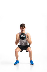Handsome hipster fitness man in gray tank top shirt and black shorts holding medicine ball, doing squat. Studio shot on gray background.