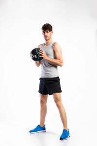 Handsome hipster fitness man in gray tank top shirt and black shorts holding medicine ball. Studio shot on gray background.