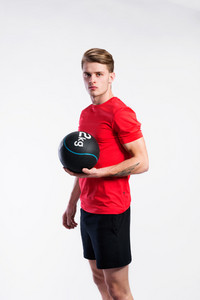 Handsome hipster fitness man in red t-shirt holding medicene ball. Studio shot on gray background.