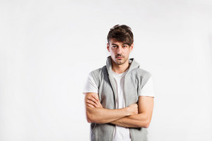 Handsome hipster fitness man in white t-hirt and gray vest with hood. Studio shot on gray background. Arms crossed.