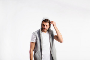 Handsome hipster fitness man in white t-hirt and gray vest with hood. Studio shot on gray background.