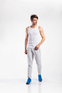 Handsome hipster fitness man in white tank top shirt and gray sweatpants. Studio shot on gray background.