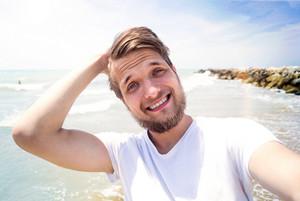 Handsome hipster man in white t-shirt on beach, smiling, taking selfie. Enjoying time at seaside.