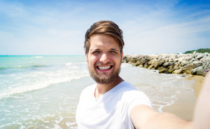 Handsome hipster man in white t-shirt on beach, smiling, taking selfie. Enjoying time at seaside.