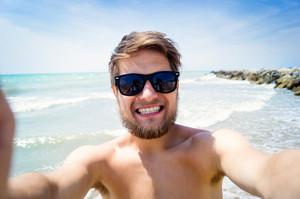Handsome hipster man on beach, wearing sunglasses, smiling, taking selfie. Enjoying time at seaside.