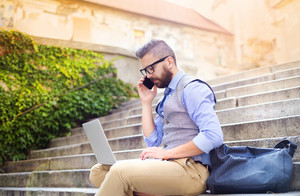 Handsome hipster modern businessman using smart phone and laptop in the city