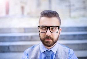 Handsome hipster modern businessman with beard and glasses in town