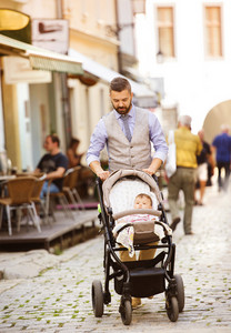 Handsome hipster modern businessman with beard walking with baby in pram in town