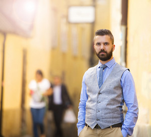 Handsome hipster modern businessman with beard walking in town