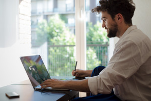 handsome hipster modern man designer working home using laptop at home