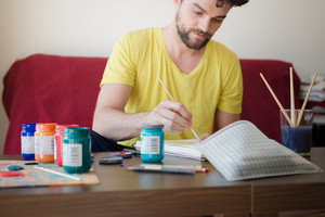 handsome hipster modern man painting at home