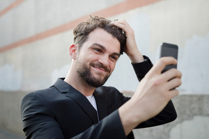 handsome hipster modern man using smart phone selfie in the city
