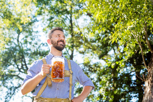 Handsome hipster young man in traditional bavarian clothes holding a mug of beer, arm on hip. Oktoberfest. Sunny summer garden.