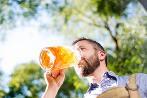 Handsome hipster young man in traditional bavarian clothes holding a mug of beer, drinking. Oktoberfest. Sunny summer garden.