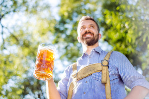 Handsome hipster young man in traditional bavarian clothes holding a mug of beer. Oktoberfest. Sunny summer garden.
