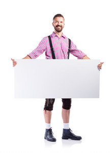 Handsome hipster young man in traditional bavarian clothes holding empty white board, copy space. Oktoberfest. Studio shot on white background, isolated.