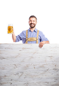 Handsome hipster young man in traditional bavarian clothes standing behind wooden planks, holding a mug of beer, copy space. Oktoberfest. Studio shot on white background, isolated.