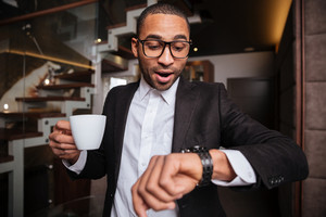 Handsome Late african man in suit with cup of coffee in hand looking at wristwatch in hotel