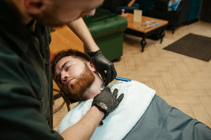 Handsome man getting beard shaving by hairdresser while lies in chair at barbershop.