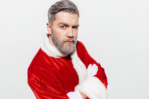 Handsome man santa claus standing with hands folded