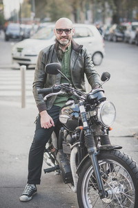 handsome middle aged man motorcyclist in the city