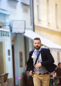 Handsome modern hipster businessman with bag hurrying to work
