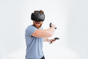 Handsome playful bearded man wearing virtual reality device standing over white background while holding joysticks in hands.