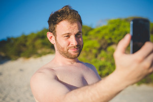 handsome redhead bearded man taking selfie with smartphone at the beach in summertime