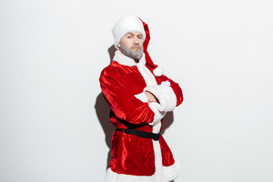 Handsome santa claus standing with arms crossed over white background