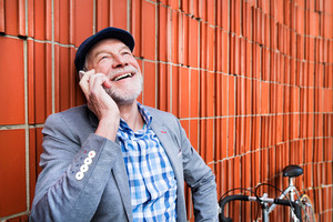 Handsome senior man in blue checked shirt and gray jacket with bicycle holding smart phone, making phone call. Orange brick wall background.