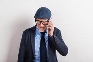 Handsome senior man in blue shirt, jacket, black eyeglasses and flat cap holding smart phone, making phone call. Studio shot against white wall.