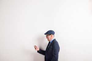 Handsome senior man in blue shirt, jacket, black eyeglasses and flat cap holding smart phone. Studio shot against white wall.
