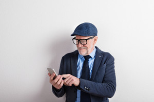 Handsome senior man in blue shirt, jacket, black eyeglasses and flat cap holding smart phone, texting. Studio shot against white wall.