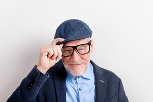 Handsome senior man in blue shirt, jacket, black eyeglasses and flat cap. Studio shot against white wall.