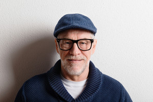 Handsome senior man in blue sweater, flat cap and black eyeglasses. Studio shot against white wall.