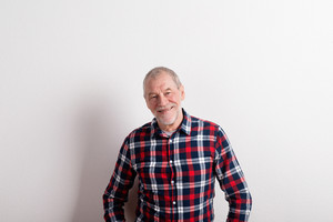 Handsome senior man in checked shirt smiling. Studio shot against white wall.
