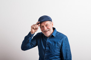 Handsome senior man in denim shirt and flat cap smiling. Studio shot against white wall.