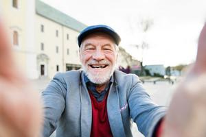 Handsome senior man in gray jacket and flat cap in town taking selfie of himself.