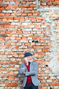 Handsome senior man in gray jacket holding smart phone, making phone call. Orange brick wall background.